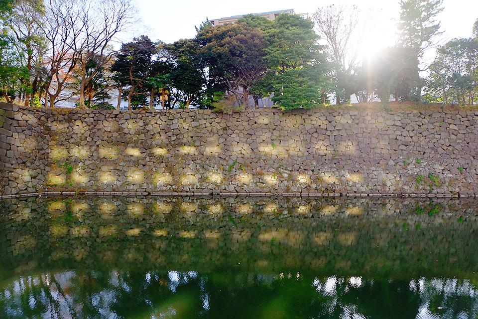 四角のマス目模様は、太陽の光が近隣のビルの窓を照らして、それが石垣を照らし、さらに水面へと反射してできたものです。