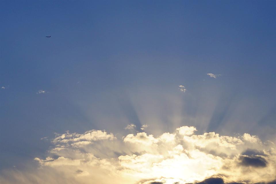 雲間から溢れる光線と飛行機