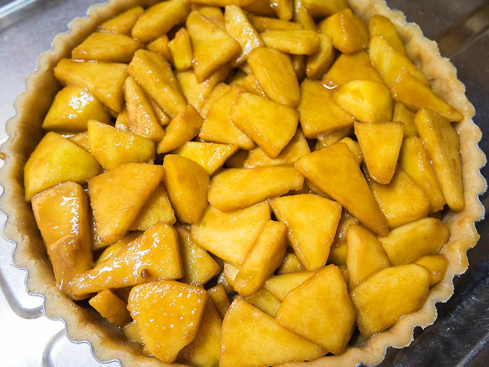 りんごに砂糖などをまぶして生のままパイ生地に重ねます。