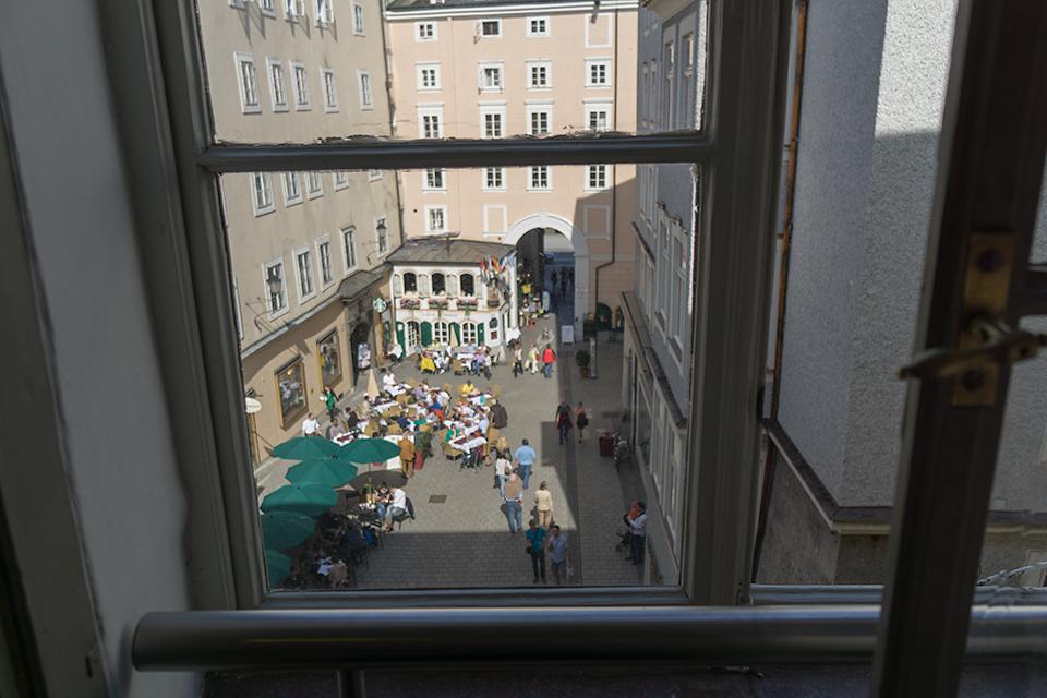 モーツアルトの生家の窓からのぞく外の風景。当時もこんな風に賑わっていたのでしょうか。